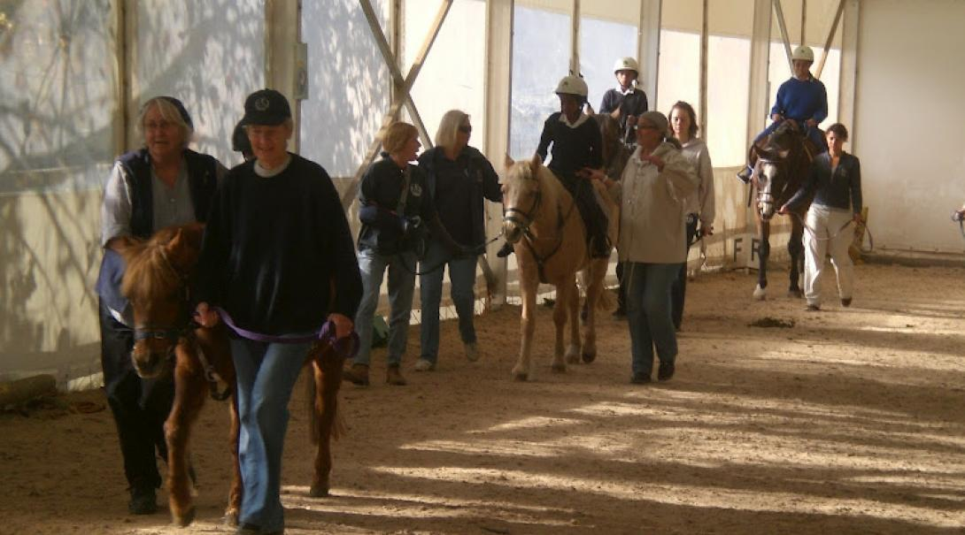 Equine Therapy interns walk with children and horses at a therapy centre in Cape Town, South Africa.
